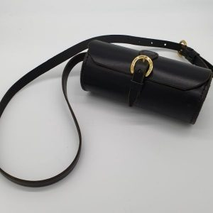Small, black, cylindrical leather shoulder bag with brass buckles.