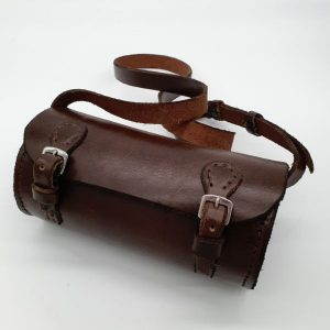 Brown, cylindrical leather shoulder bag with bridle buckles.